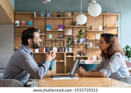 Indian male hr specialist manager, employer, boss listening female latin candidate at job interview, consulting client at office meeting. Hiring and employment, human resources, recruitment concept. Royalty-Free Stock Photo #1935739312