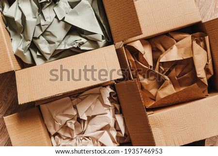 Cardboard boxes with crumpled paper inside for packaging goods from online stores, eco friendly packaging made of recyclable raw materials Royalty-Free Stock Photo #1935746953