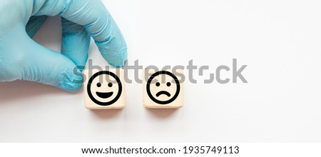 Close up custome choose smiley face and sad face icon on wood cube, Service rating, satisfaction concept. banner.