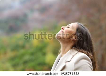 Profile of a satisfied middle aged woman breathing fresh air in a forest in winter Royalty-Free Stock Photo #1935751552