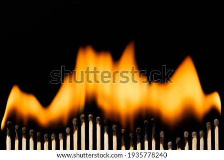 Line of burning matches. Many matches placed in a row that goes up and down on a black background Royalty-Free Stock Photo #1935778240