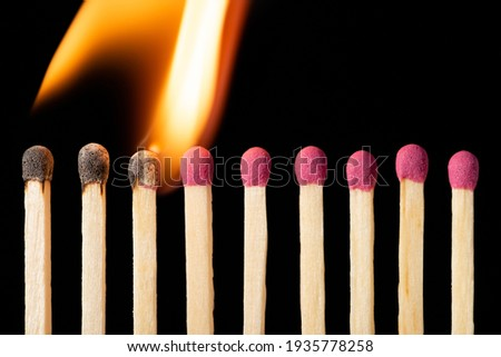 Line of matches igniting one by one. Burning matches on the black background Royalty-Free Stock Photo #1935778258