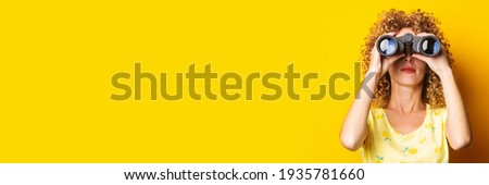 curly-haired girl looks through binoculars on a bright yellow background. Banner Royalty-Free Stock Photo #1935781660