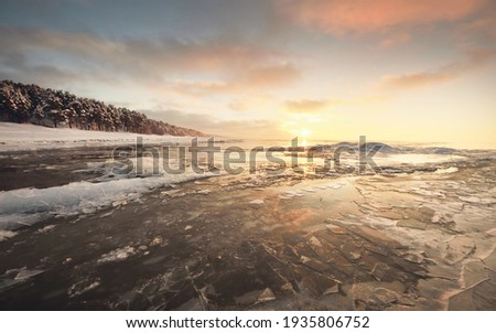 Frozen Baltic sea shore at sunset. Ice fragments close-up, snow-covered pine forest in the background. Colorful cloudscape. Symmetry reflections on the water.   Royalty-Free Stock Photo #1935806752