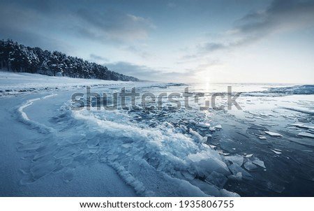 Frozen Baltic sea shore at sunset. Ice fragments close-up, snow-covered pine forest in the background. Colorful cloudscape. Symmetry reflections on the water. Nature, climate change. Panoramic view Royalty-Free Stock Photo #1935806755