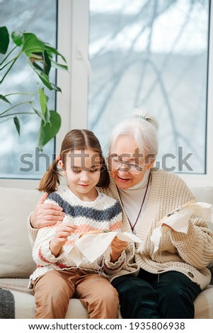 Proud granny sitting on a couch with her granddaughter. they are embroidering on a loop together. She's hugging and encouraging her.
