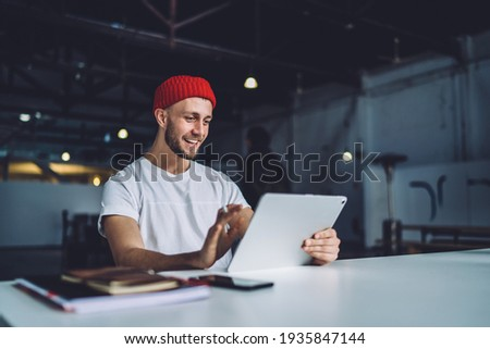 Positive male editor in trendy cap sitting at desktop with modern touch pad wathcing video before online montage via application, happy man in stylish outfit reading good news on content website