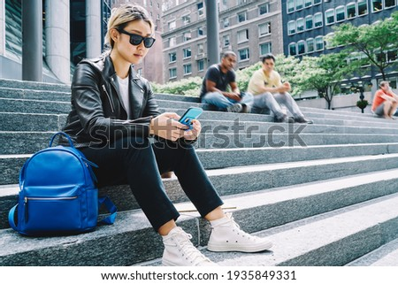 Asian hipster girl in trendy sunglasses jacket using mobile device for reading travel publication in social media, millennial tourist connecting to 4g internet for browsing web text via smartphone Royalty-Free Stock Photo #1935849331