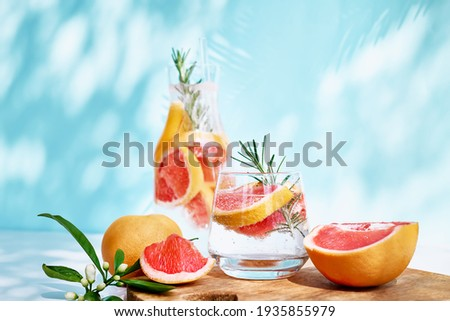 Summer cocktail with grapefruit and rosemary and juicy slices citrus fruits. Fresh healthy grapefruit beverage on sunlight with shadows. Creative drink on blue pastel background. Royalty-Free Stock Photo #1935855979