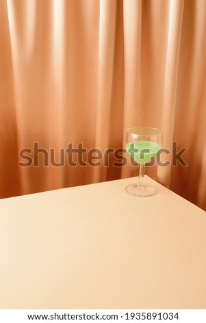 A glass on the corner filled with a green drink. Cream curtain in the background. Big copy space for different purposes. Simple creative lifestyle 2021 concept. Trendy colors.