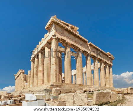 Acropolis, ancient Greek fortress in Athens, Greece. Panoramic image of Parthenon temple on a bright day with blue sky and faraway clouds. Classical Greek heritage