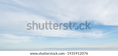 Blue sky against soft white clouds. Beautiful natural cloudscape background. Royalty-Free Stock Photo #1935912076