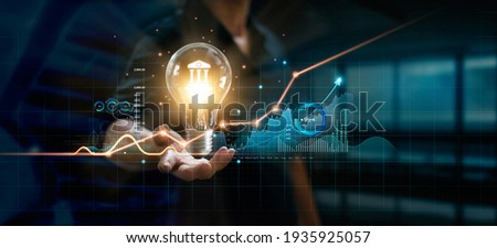 Businessman holding creative light bulb with growth graph and banking icons. Financial innovation technology develop new products and services that enhance successful and profit in global business. Royalty-Free Stock Photo #1935925057
