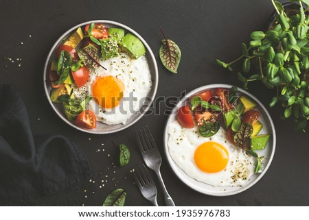 Sunny side up egg breakfast with avocado salad on plate, top view. Healthy breakfast food Royalty-Free Stock Photo #1935976783