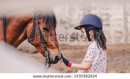 Asian school kid girl with horse ,riding or practicing horse ridding at horse ranch