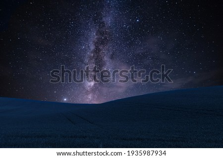 Night landscape with field on hills and Milky way sky Royalty-Free Stock Photo #1935987934