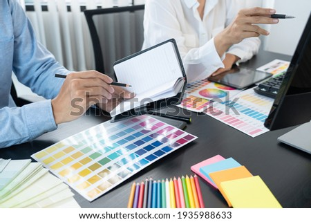 graphic designer team working on web design using color swatches editing artwork using tablet and a stylus at desks In creative office. Royalty-Free Stock Photo #1935988633