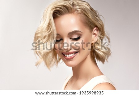 Beautiful model girl with short hair .Beauty  smiling woman with blonde curly hairstyle dye .Fashion, cosmetics and makeup Royalty-Free Stock Photo #1935998935