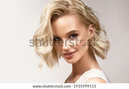 Beautiful model girl with short hair .Beauty woman with blonde curly hairstyle dye .Fashion, cosmetics and makeup Royalty-Free Stock Photo #1935999115
