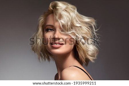 Beautiful model girl with short hair .Beauty  smiling woman with blonde curly hairstyle dye .Fashion, cosmetics and makeup Royalty-Free Stock Photo #1935999211