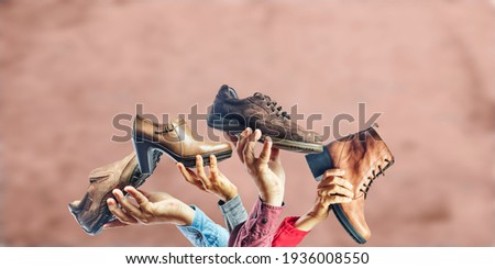 Hands holding different men and women shoes and boots. Concept of selection, purchase and repair of shoes. Royalty-Free Stock Photo #1936008550