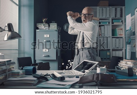 Crazy stressed businessman destroying his desk and laptop with a baseball bat, job burnout concept Royalty-Free Stock Photo #1936021795
