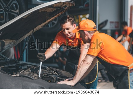 Car mechanics open car hood repairs system checking oil motor level for maintenance and clean in car garage service. Royalty-Free Stock Photo #1936043074