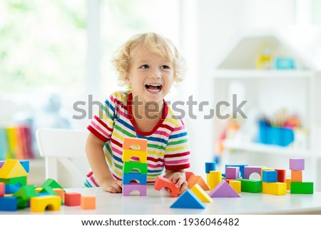 Kid playing with colorful toy blocks. Little boy building tower of block toys. Educational and creative toys and games for young children. Baby in white bedroom with rainbow bricks. Child at home. Royalty-Free Stock Photo #1936046482
