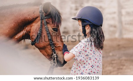 Asian school kid girl with horse, riding or practicing horse riding at a horse ranch