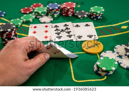 player shows two play card aces on a green table in a casino wirh chips. gambling Royalty-Free Stock Photo #1936085623