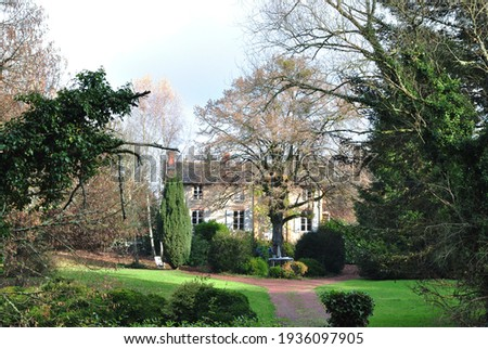 Old French Farmhouse and and Deserted Drive with Wooded Garden  Royalty-Free Stock Photo #1936097905