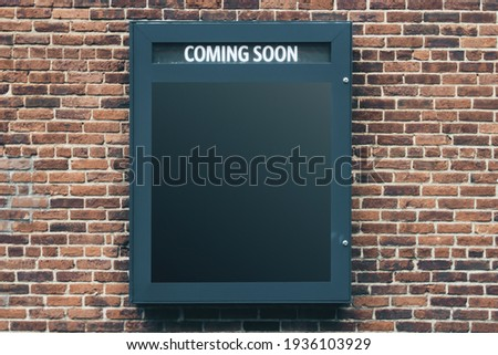 Blank black poster coming soon on old brick wall, mockup