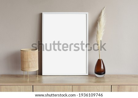 Blank white empty picture frame mockup on grey wall. Copy space. Artwork showcase. View of modern scandinavian style interior with chair. Home staging and minimalism concept Royalty-Free Stock Photo #1936109746
