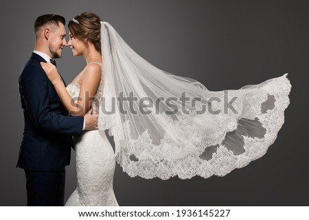 Wedding Couple Dancing. Romantic Bride and Groom Portrait. Bridal long Veil flying over Gray Studio Background Royalty-Free Stock Photo #1936145227