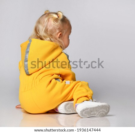 Child in seasonal sports outerwear sits with his back to the camera. Little toddler girl in a yellow warm sports suit sitting on a gray background. Concept of stylish sportswear. Place for text. Royalty-Free Stock Photo #1936147444