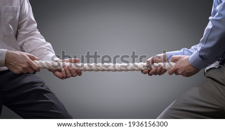 Two businessmen pulling tug of war with a rope concept for business competition, rivalry, challenge or dispute Royalty-Free Stock Photo #1936156300