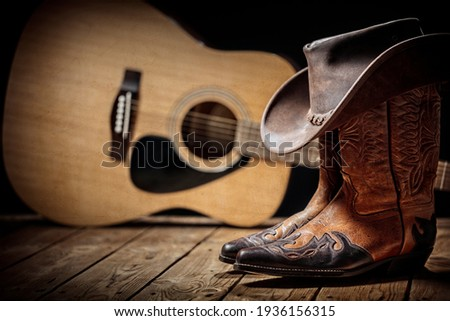 Country music festival live concert with acoustic guitar, cowboy hat and boots background Royalty-Free Stock Photo #1936156315