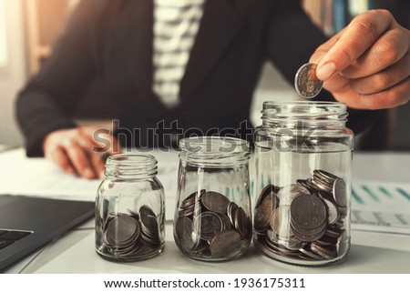 saving money with hand putting coins in jug glass concept financial Royalty-Free Stock Photo #1936175311
