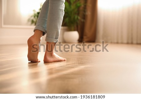 Barefoot woman at home, closeup. Floor heating system Royalty-Free Stock Photo #1936181809