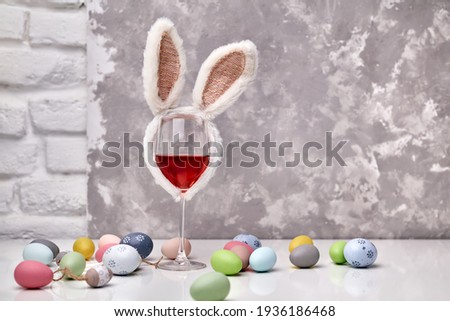 Glass of rose or red wine with bunny ears and Easter decorations, colorful eggs on white table, on bright background. Copy space for text. Royalty-Free Stock Photo #1936186468