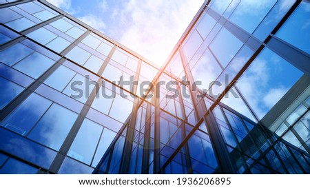 Modern office building with glass facade on a clear sky background. Transparent glass wall of office building. Royalty-Free Stock Photo #1936206895