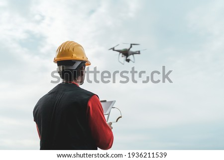 Male engineer monitoring construction site with drone - Technology and industrial concept