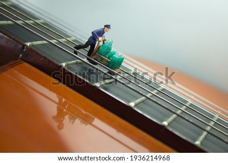 View of a miniature luggage rack with a handcart full of luggage that descends on a guitar neck between the strings fret by fret. White Background Royalty-Free Stock Photo #1936214968