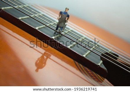 View of a section of an acoustic guitar where a miniature figure pulls a handcart behind it and walks over the guitar strings. White background Royalty-Free Stock Photo #1936219741
