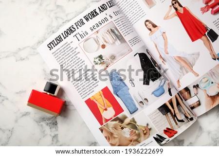 Open fashion magazine and perfume on white marble table, flat lay Royalty-Free Stock Photo #1936222699