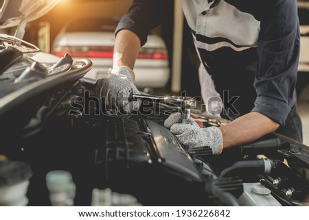 Automobile mechanic repairman hands repairing a car engine automotive workshop with a wrench, car service and maintenance,Repair service. Royalty-Free Stock Photo #1936226842