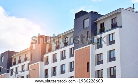 Futuristic square architecture of apartment building. Real estate with panoramic windows and blue sky with clouds. Royalty-Free Stock Photo #1936228600