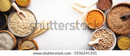 Organic products. Bowls with different gluten free grains on white background, top view Royalty-Free Stock Photo #1936241101