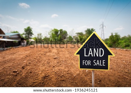 land for sale sign against trimmed lawn background. Empty dry cracked swamp reclamation soil, land plot for housing construction project in rural area and beautiful blue sky with fresh air.