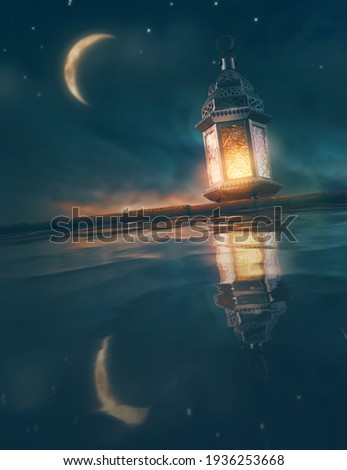 Ornamental Arabic lantern with burning candle glowing at night. Festive greeting card, invitation for Muslim holy month Ramadan Kareem. Royalty-Free Stock Photo #1936253668